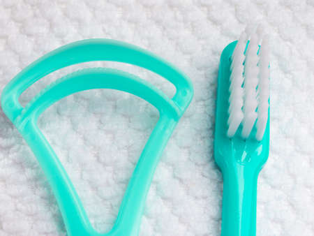 tongue cleaner: Oral hygiene health concept. Closeup dental tools green toothbrush and tongue cleaner on white towel