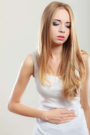 bellyache: Bellyache, indigestion or menstruation. Young woman suffering from stomach pain studio shot on gray Stock Photo