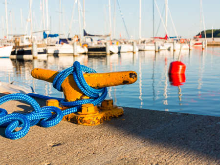 Yellow mooring bollard with blue rope in marina yachts in the background Stock Photo