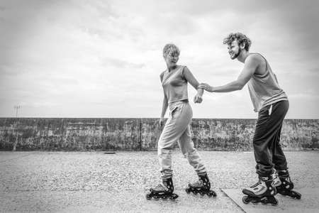 rollerblades: Exercising and competition in sport. Healthy lifestyle and wellbeing. Summertime hobby. Young people race together on rollerblades having fun black and white.