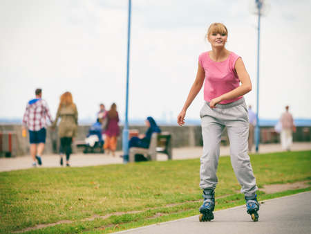rollerblades: Outdoors activities sport and hobby.Wellbeing and exercising. Girl have fun riding rollerblades in park spending free time in summer. Stock Photo