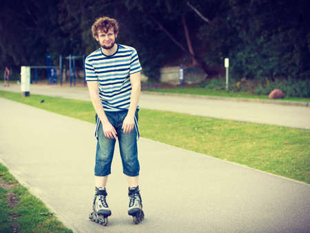 rollerskates: Holidays, active lifestyle freedom concept. Young fit man on roller skates riding outdoors on street, guy rollerblading on sunny day