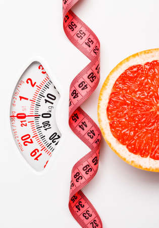 Concepto de dieta baja delgada comer sano. Rodaja de pomelo primer con cinta de medición en la escala de peso blanco