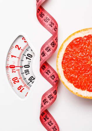 Op dieet zijn gezond eten afslanken concept. De grapefruitplak van de close-up met het meten van band op witte gewichtsschaal