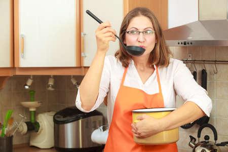 ama de casa: El ama de casa cena degustaci�n comida sopa. mujer de mediana edad que sostiene la cuchara cuchara y bote. Ama de llaves que llevaba el delantal de color naranja de preparar los alimentos. Foto de archivo