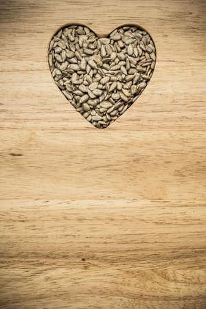whole food: Whole food. Heart shaped sunflower seeds on wood surface background