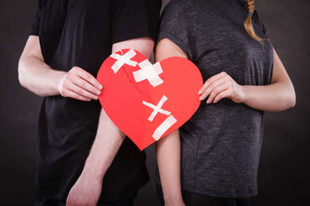 Broken heart difficult love concept. Couple woman and man hands holding paper red heart fixed with plaster bandage. Rift in relations. Stock Photo