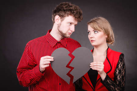 heartbreak issues: Broken heart difficult love concept. Sad unhappy couple woman and man holding paper red heart fixed with plaster bandage. Rift in relations.