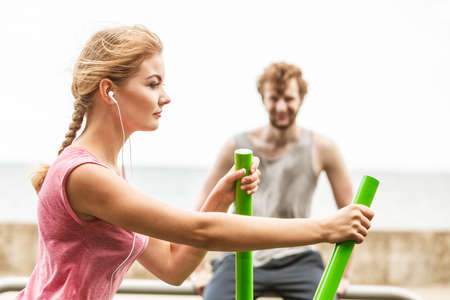 escucha activa: Active woman exercising on elliptical trainer machine and man listening to music. Fit sporty girl in training suit working out at outdoor gym. Sport fitness and healthy lifestyle concept.