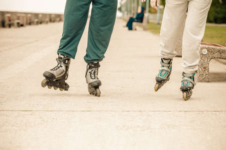 rollerblades: Spending free time together in summer. Hobby and lifestyle. Exercising and healthy body. Close up of legs in sportswear riding rollerblades.