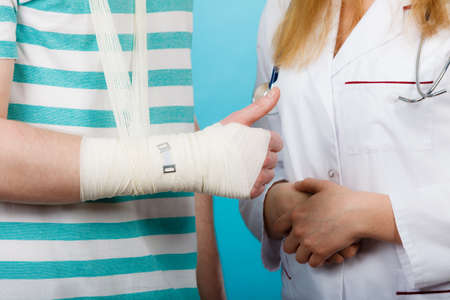 broken wrist: Healthcare and protection. Young man with broken hand sprained wrist visit female doctor. Specialist with bandage.