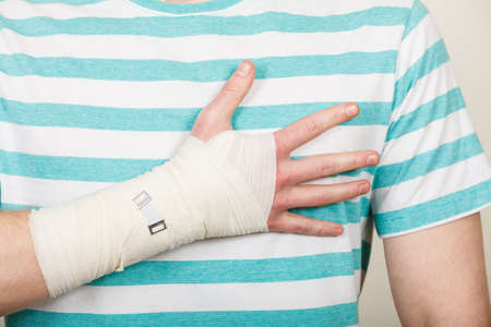 luxacion: Las fracturas y dislocaciones concepto. Parte del cuerpo masculino con la mano en el vendaje. medicamentos útiles para el brazo de palma dolorosa de la joven.
