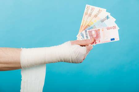 white bandage: Corruption in healthcare industry. Part body male bandaged hand with money and long white bandage on blue. Stock Photo