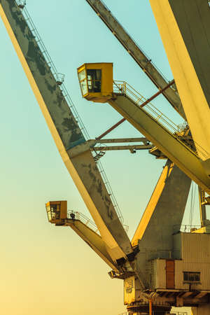 dockside: Business and commerce. Heavy load dockside cranes in port, cargo container yard. Industrial scene