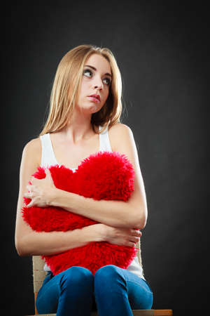 heartbreak issues: Broken heart love concept. Sad unhappy woman sitting on chair hugging red heart pillow dark background