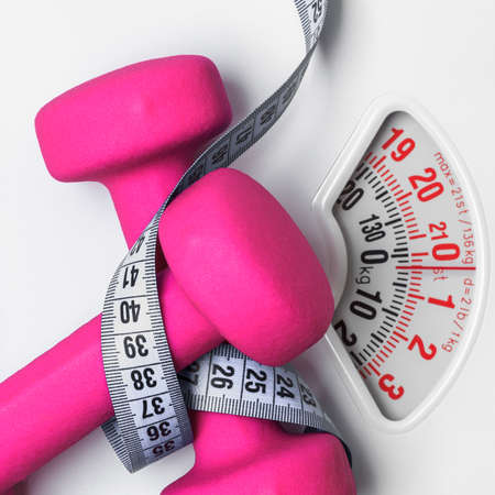 healthy lifestyle fitness weight control concept. Closeup pink dumbbells with measuring tape on white scales Archivio Fotografico