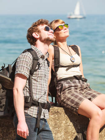 backpackers: Two young people tourists hiking by sea ocean water. Backpackers couple on summer vacation trip journey. Stock Photo