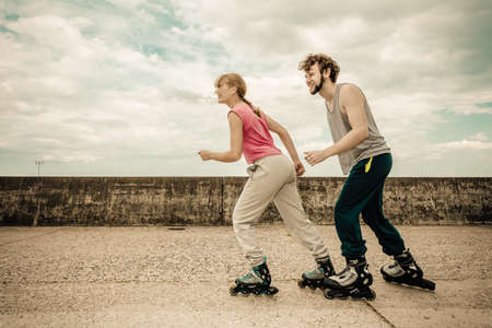 rollerblades: Exercising and competition in sport. Healthy lifestyle and wellbeing. Summertime hobby. Young people race together on rollerblades having fun.
