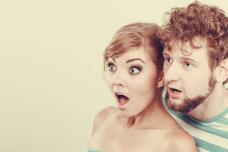 facial expression: Emotional facial expression wide eyed couple, woman an man looking surprised open mouth
