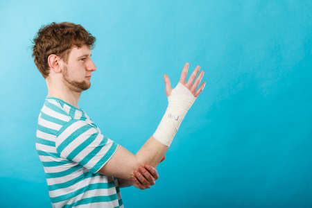 dislocation: Fractures and dislocations concept. Man with hand in bandage. Helpful medication for painful palm arm of young guy.