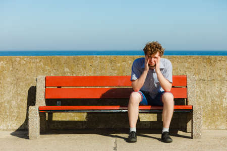 drained: Tired exhausted man sitting on bench by sea ocean. Young guy relaxing outdoor. Summer vacation. Stock Photo