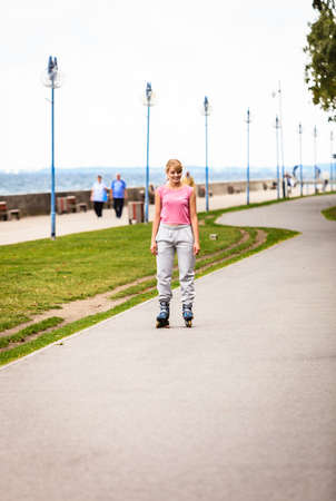 rollerskating: Active young woman in training suit rollerskating outdoor. Girl riding enjoying sport. Stock Photo