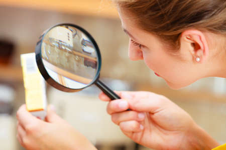 food testing: Mature woman female inspecting testing butter food label with magnifying glass.