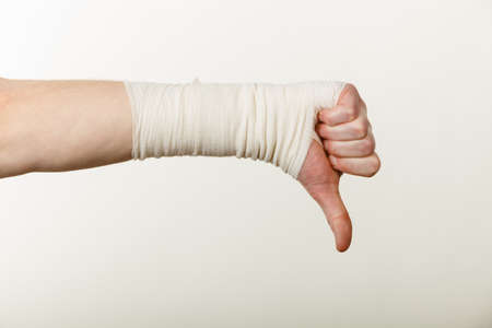 aspects: Bad news and information. Medicine aspects. Male hand with bandage showing thumb down sign symbol.