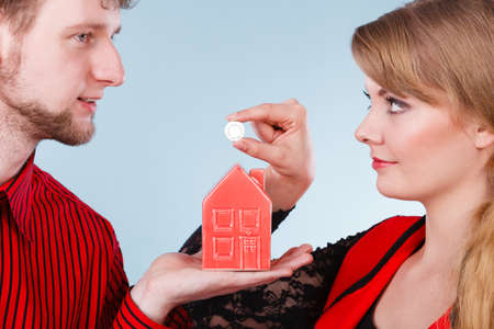 better price: Savings for future plans. Couple with red little house piggy bank and silver coin. Money loin for family home better life. Stock Photo