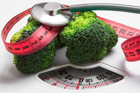 Diet healthy eating weight control concept. Closeup green broccoli with measuring tape and stethoscope on white scales