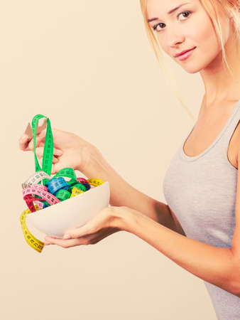 losing control: Diet, healthy eating, weight loss and slim body concept. Fit fitness girl holding bowl with many colorful measuring tapes Stock Photo