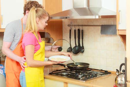 breaded: Couple frying breaded chicken cutlet on fry pan.