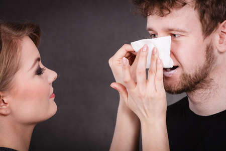 hygienic: Smiling happy woman wipe cream face nose of funny man by hygienic tissue. Girlfriend takes care of her boyfriend. Stock Photo
