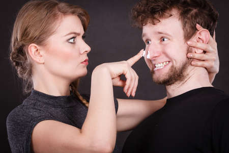 uncomfortable: Stubborn girlfriend trying to apply cream on her boyfriend face. Man in uncomfortable situation with overprotective woman.