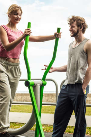 escucha activa: Mujer activa que ejercita en la m�quina el�ptica y el hombre escucha m�sica. Foto de archivo