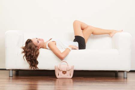 female legs: Girl in fashionable clothes posing on sofa bag handbag on floor. Stock Photo