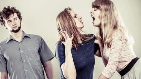 catfight: Aggressive mad women fighting over man. Stock Photo