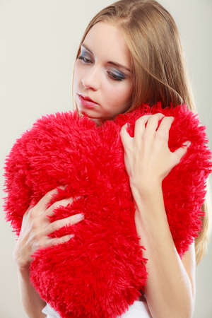 heartbreak issues: Broken heart love concept. Sad unhappy woman hugging red heart pillow closeup Stock Photo