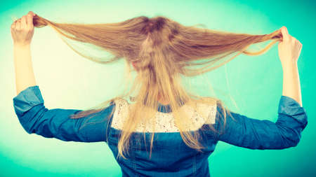 back straight: Back view of blonde woman playing with straight long hair.