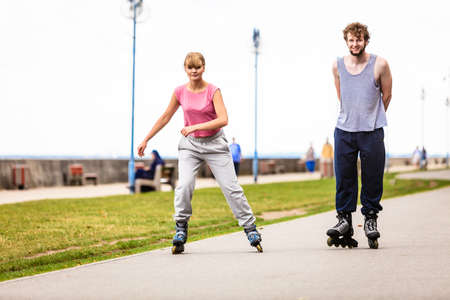 rollerskating: Young couple have fun together rollerskating in park.