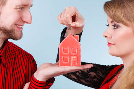 better price: Couple with red little house piggy bank and silver coin. Stock Photo