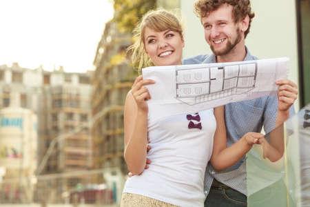 joven pareja mirando a los planes de construcción de proyectos modelo soñando con nueva casa en la zona residencial moderna, obra en construcción en el fondo
