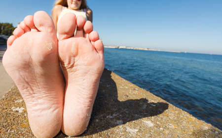 Woman relaxing outdoor by seaside showing her dry feet sole, wide angle view Stock Photo