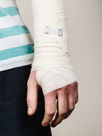 fractures: Fractures and dislocations concept. Part body male with hand in bandage. Helpful medication for painful palm arm of young man. Stock Photo
