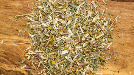 pile of leaves: Heap pile of dried herb leaves on wooden surface.