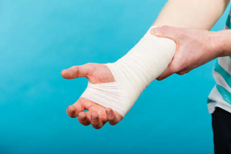 injure: Young man holds bandaged hand.