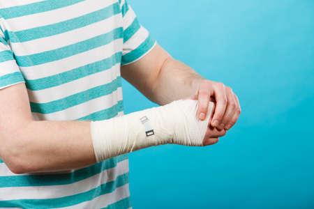 bandaged: Young man holds bandaged hand.
