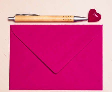 greetings card: Pink blank envelope little heart and pen on wooden surface. Valentine day card, love or wedding greeting concept.