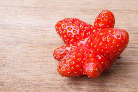 odd: Red odd single strawberry fruit on wooden table board copy space text area Stock Photo