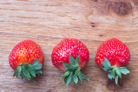 space text: Red fresh strawberry fruits on wooden table board copy space text area Stock Photo